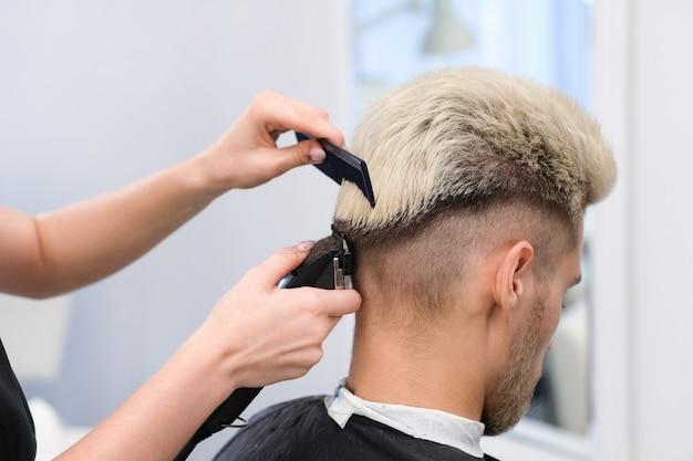 理髪店サロン、男性と男の子のための理髪店のコンセプトのアームチェアでバリカンと金髪の若い男のヘアカットプロセス