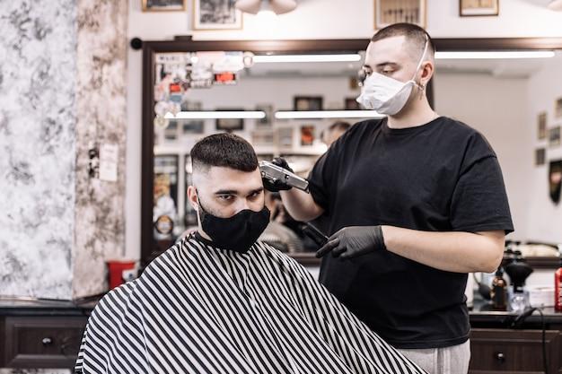 Haircut in quarantine. haircut in masks from the virus. hair and health care. man haircut in