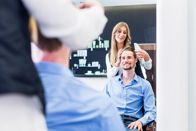 Haircutter cutting hair, shot in mirror