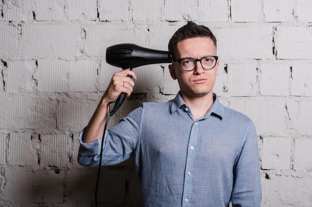 Hairdraierと灰色のレンガの壁に面白い表現を持つクレイジースタイリッシュな若者