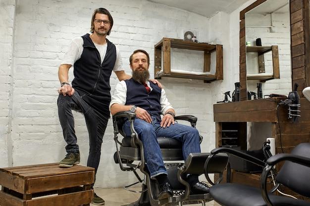 Парикмахер и бородатый молодой парень позируют перед камерой перед стрижкой.