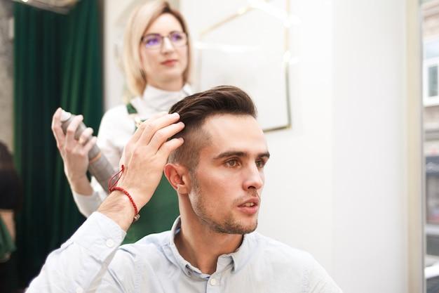 Парикмахер и клиент оценивают результат после стрижки. стилист делает прическу для парня