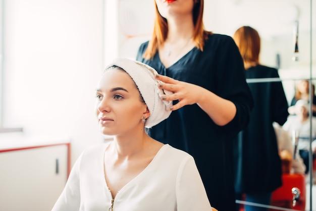 美容師と女性のクライアント、ヘアカラープロセス、美容院。ビューティーサロンでのヘアスタイル作り