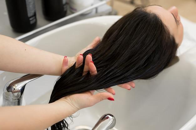 美容師は女の子の髪に治療用マスクを適用します