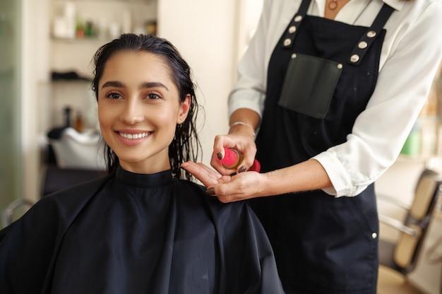 미용사는 여성의 머리카락, 정면도, 미용실에 무스를 적용합니다. 헤어 살롱의 스타일리스트와 클라이언트. 뷰티 사업, 전문 서비스