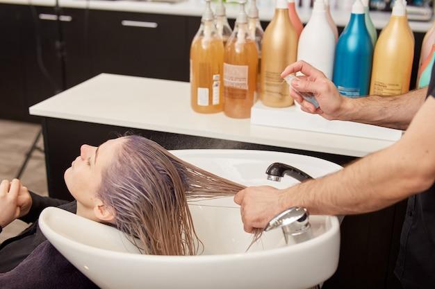 염색 및 토닝 후 여성의 머리카락에 모발액을 바르는 미용사