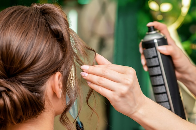 Hairdresser applying hair spray on brunette hair.