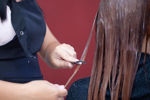 Hairdresser applying hair treatment. applying color cream at hair.