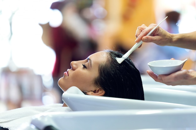 The hairdresser applying hair treatment for customer in a beauty salon.