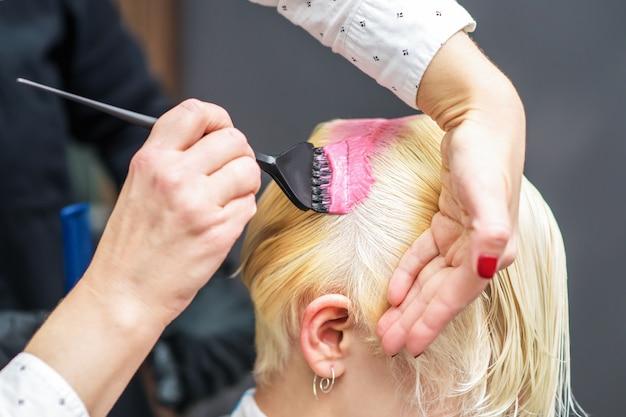 Парикмахер, применяя розовый краситель для волос женщины.