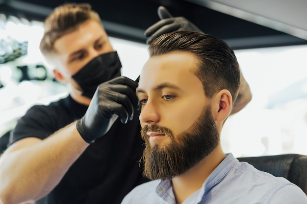 Hairdresser or barber combs man's hair while making a hairstyle in modern barbershop