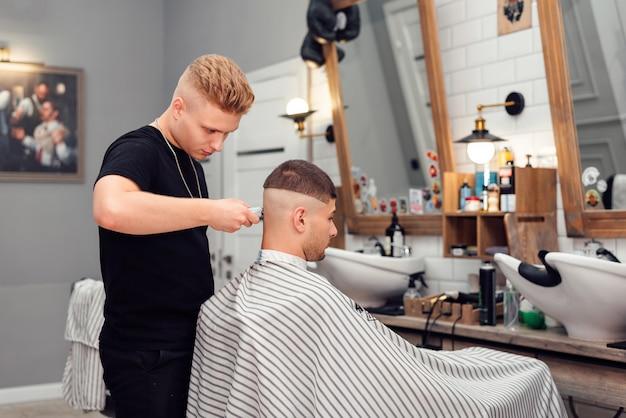 Парикмахер-парикмахер режет клиента в салоне
