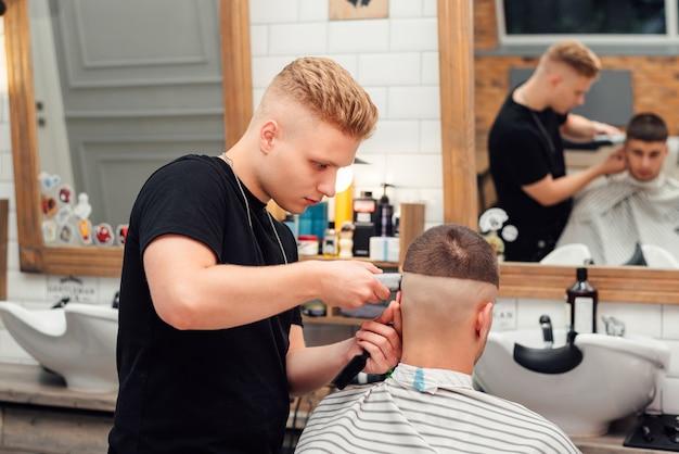 Hairdresser barber cuts client in salon