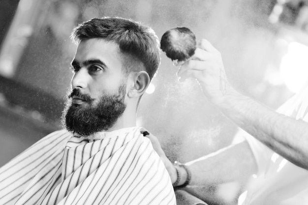 Hairdresser or barber does a hairstyle to a young man with a beard and mustache and pours talc on his hair