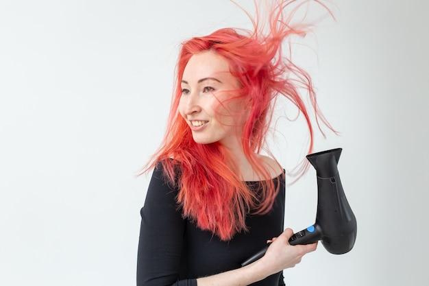 美容院、美容院、人々のコンセプト-白い背景にヘアドライヤーを持つ若い女性のヘアスタイリスト。