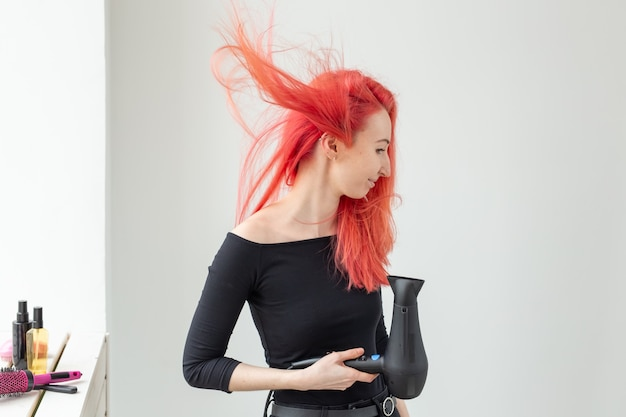 Hairdresser, beauty salon and people concept - young woman hair stylist with hair dryer on white