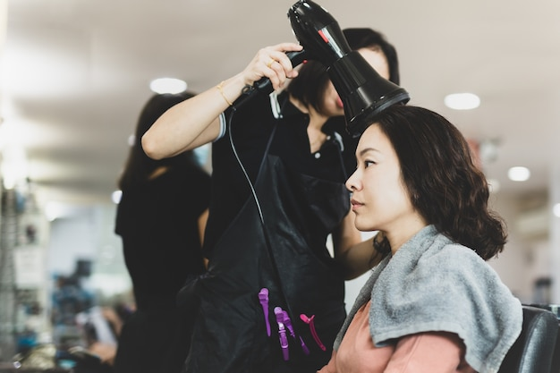 Hairdresser blow-dry hair of client in salon