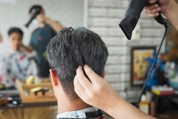 Hairdresser blow drying his client hair after finished haircut. asian young man being blow dry hair with hairdryer by professional barber in barbershop.