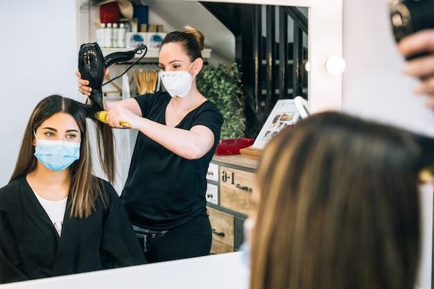 코로나 바이러스로 인해 얼굴 마스크를 쓰고 거울에 비친 긴 머리를 가진 아름다운 소녀의 머리카락을 불어 건조시키는 미용사