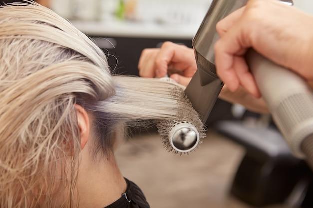 Парикмахер сушит волосы женщинами с круглой щеткой