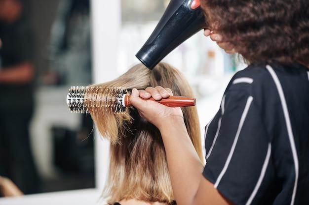 Парикмахер сушит волосы феном клиента