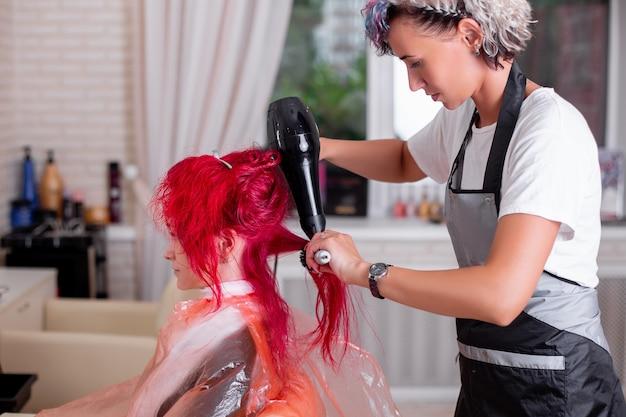 Парикмахер расчесывает и сушит розовые волосы феном