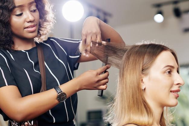 Парикмахер расчесывает волосы красивой клиентки