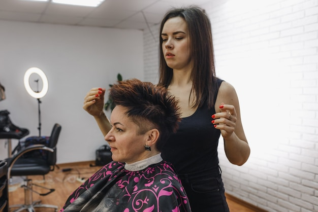 The hairdresser carefully makes a hairstyle for her client, in a beauty salon