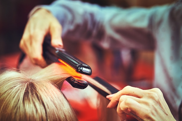 Hairdresser caring for female hair in a beauty salon.