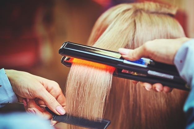 Парикмахер ухаживает за женскими волосами в салоне красоты.