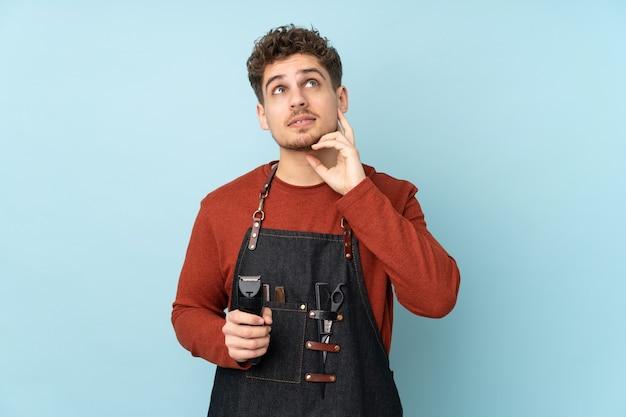 Кавказский мужчина парикмахер изолирован на синем, думая об идее