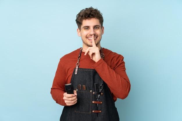 Парикмахер кавказских человек на синей стене делает жест молчания
