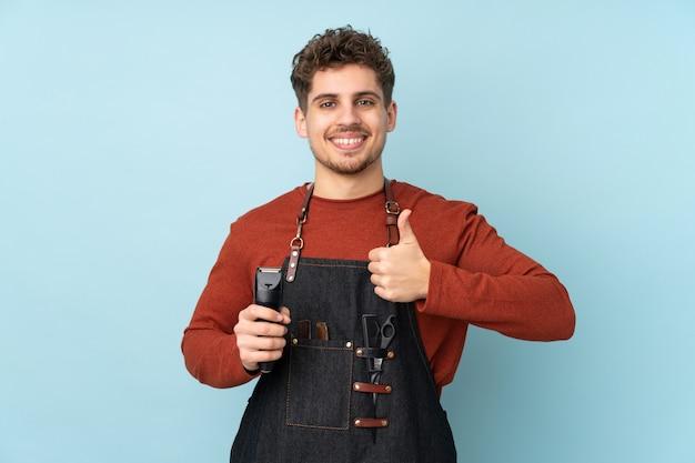 Парикмахер кавказских человек на синей стене, давая пальцы вверх жест