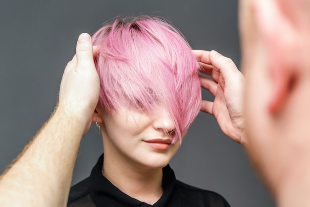 Hairdresser checking woman's pink hairstyle.