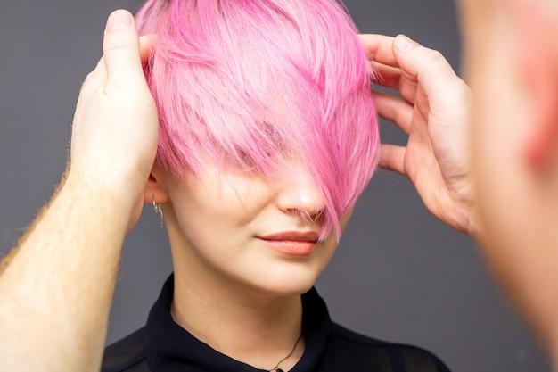 Парикмахер проверяет розовую прическу женщины.