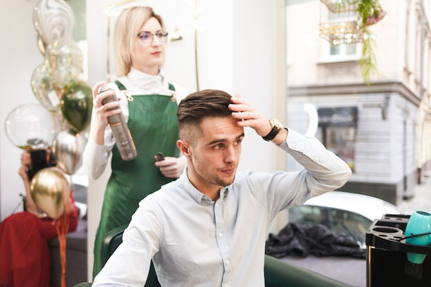 Hairdresser and client evaluate result after haircut. stylist doing hair styling for guy