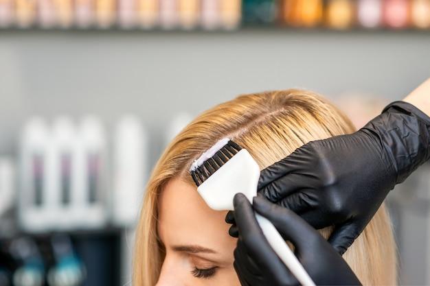 Hairdresser colors female customer hair