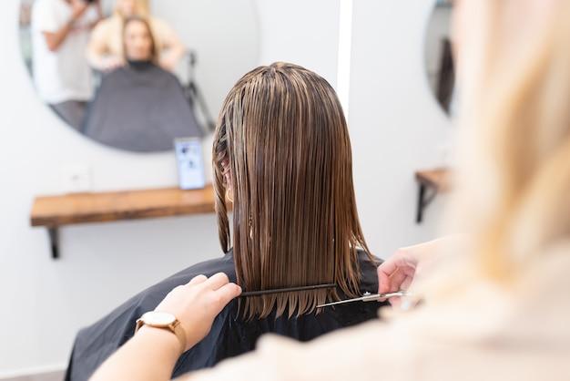 미용사는 거울을 보면서 살롱에서 고객의 젖은 머리를 빗고 자르고 있습니다.