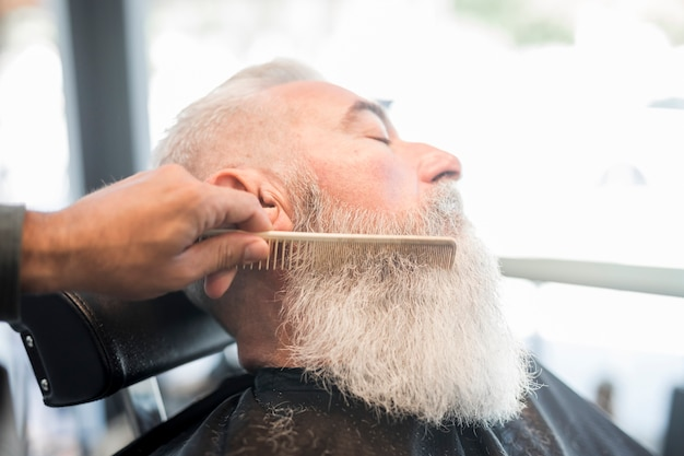 Hairdresser combing beard of aged client in barbershop