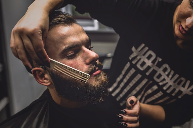 Hairdresser combing beard of stylish man