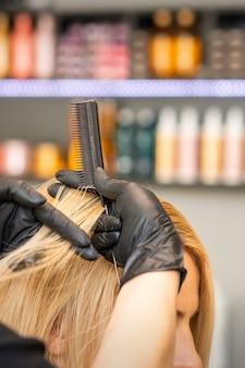 Парикмахер расчесывает женские волосы клиентов перед окрашиванием в парикмахерской