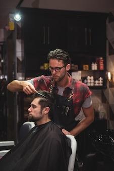 Parrucchiere che pettina i capelli dei clienti