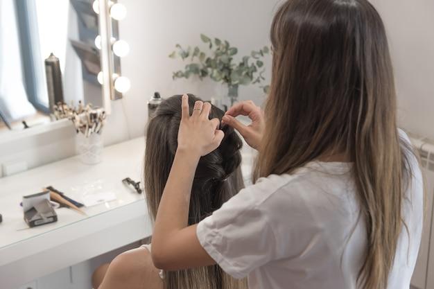 クライアントの髪をとかし、カットし、まっすぐにする美容師。美容セッション:美容師がクライアントの髪をとかし、カットし、まっすぐにします。理髪セッション。
