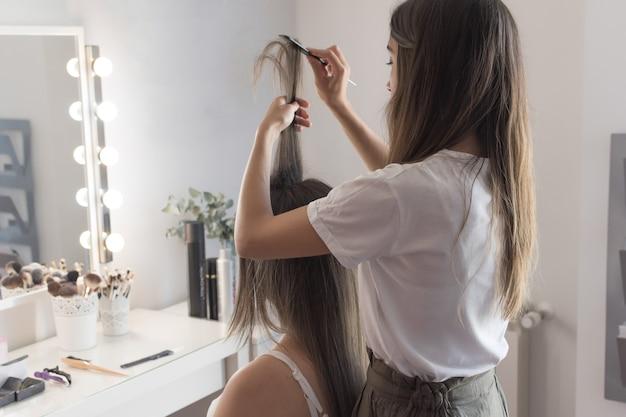 Парикмахер расчесывает, стрижет и выпрямляет волосы клиента. парикмахерская.