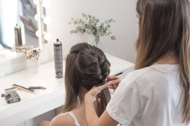 Hairdresser combing, cutting and straightening the client's hair. hairdressing session.
