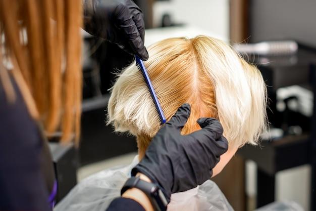 Парикмахер расчесывает короткие светлые волосы женщины перед окрашиванием в парикмахерской