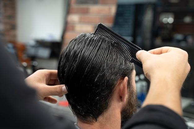 髪をとかす美容師のクローズアップ