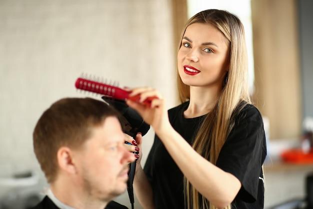 Парикмахер расчесывает мужские волосы и дует феном