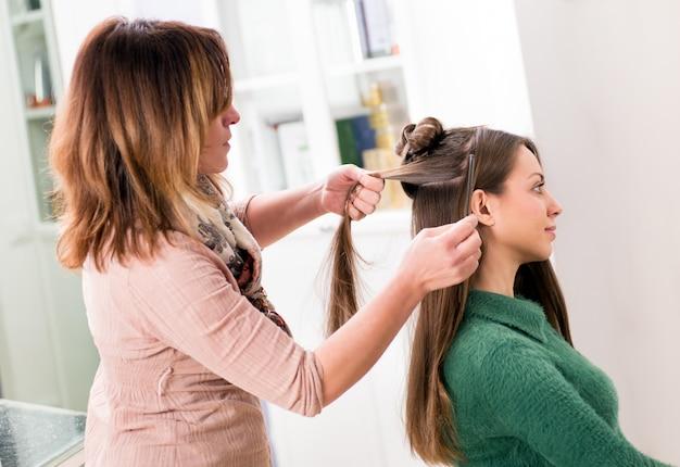 Парикмахер расчесывает длинные волосы девушки