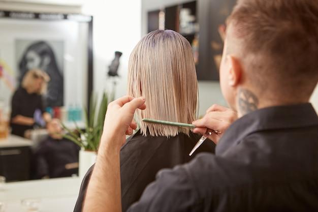 Парикмахер, расчесывающий волосы женщины в салоне красоты